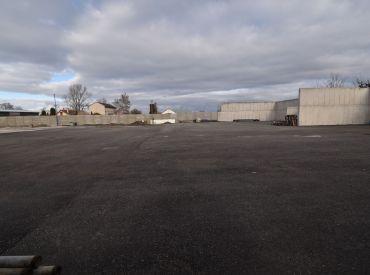 Priestranný rovinatý oplotený vyasfaltovaný pozemok, všetky IS, parkovanie pre 25 kamiónov